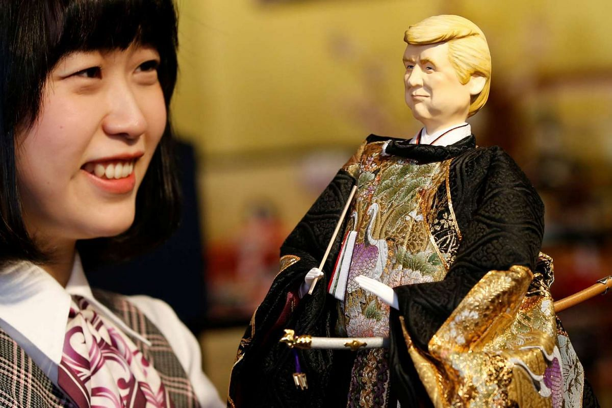 An employee of Japanese doll-maker Kyugetsu Inc poses with a doll depicting U.S. President Donald Trump, as part of a traditional set of Japanese ornamental hina dolls used in Japan to celebrate Girls' Day, at the company's main shop in Tokyo, Japan,