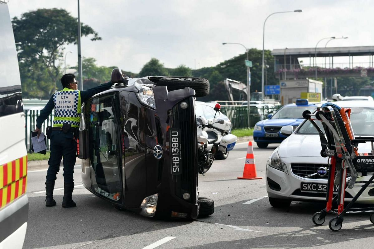 A taxi flipped onto its left side after being involved in an accident along Braddell Road this morning on January 26, 2017. PHOTO: STRAITS TIMES/JOYCE FANG