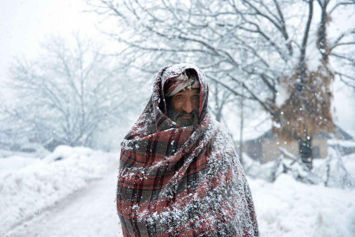 An elderly Kashmiri villager walks through snow in Gund, some 70km northeast from Srinagar, on January 25, 2017. PHOTO: AFP