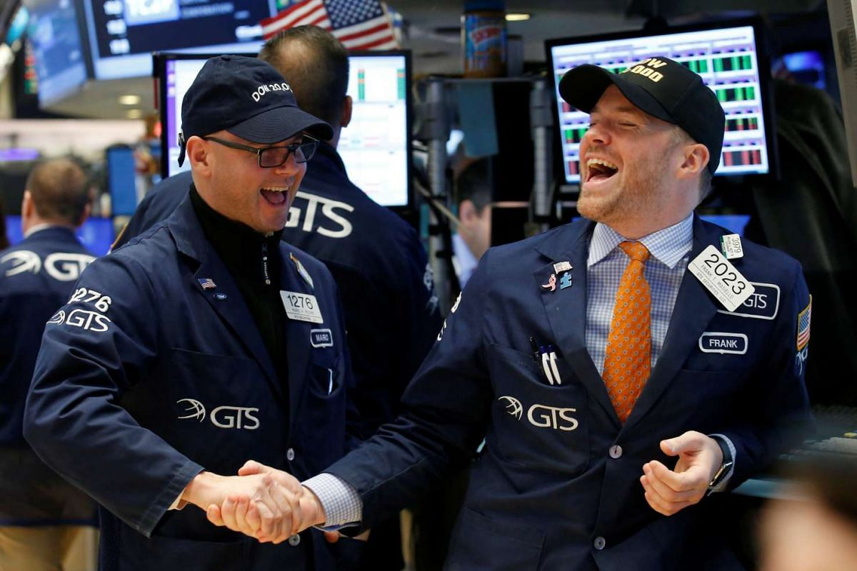 Traders celebrate on the main trading floor of the New York Stock Exchange (NYSE) as the Dow Jones Industrial Average passes the 20,000 mark shortly after the opening of the trading session in New York, U.S., January 25, 2017. PHOTO: REUTERS