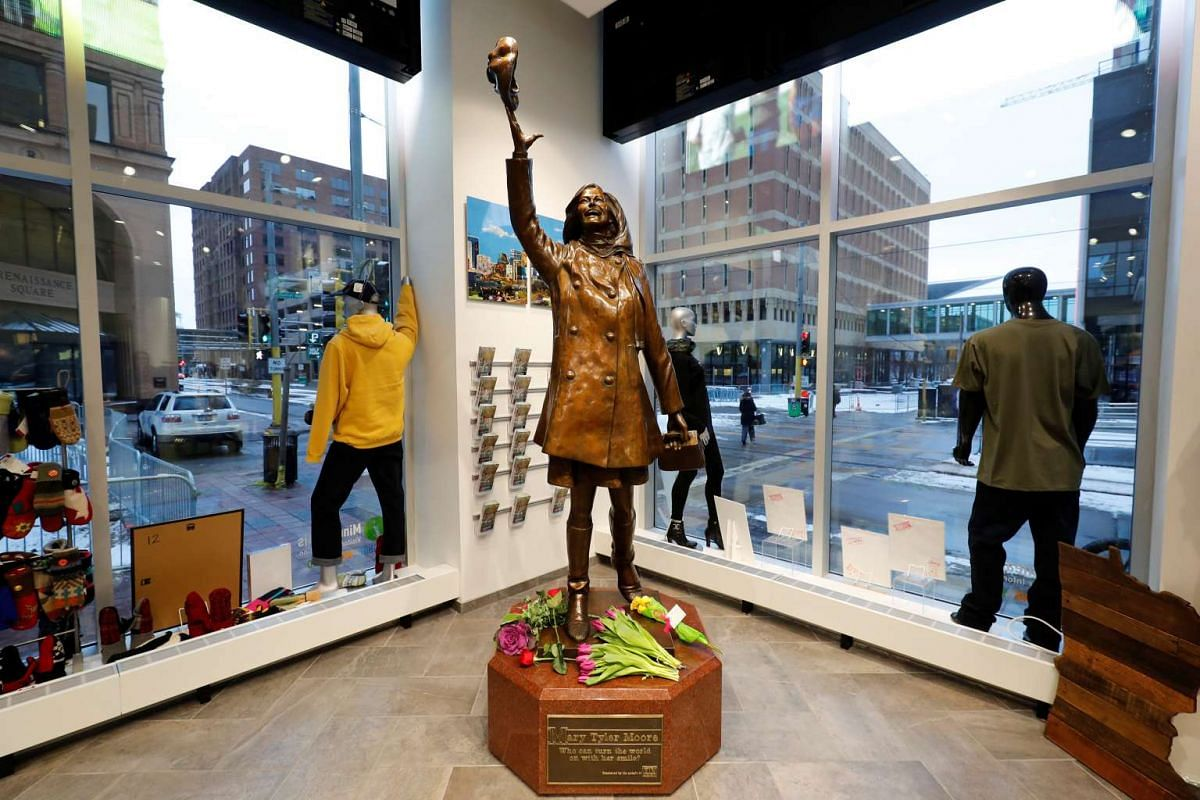 """Flowers lay at a bronze sculpture depicting actress Mary Tyler Moore from the opening credits of the television sitcom """"The Mary Tyler Moore Show"""" in Minneapolis, Minnesota, U.S., January 25, 2017. PHOTO: REUTERS"""