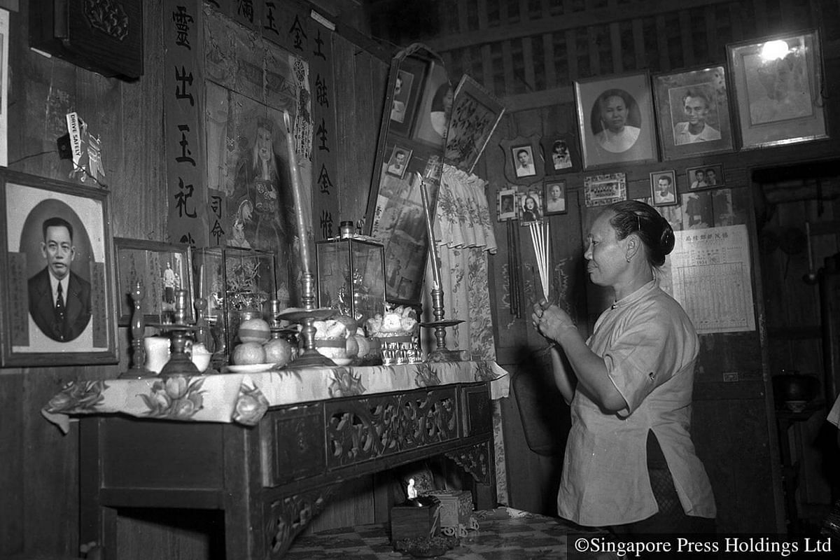 1954: A woman praying in front of her family altar. Families usually pray to their ancestors at the family shrine before they sit down for the reunion dinner.