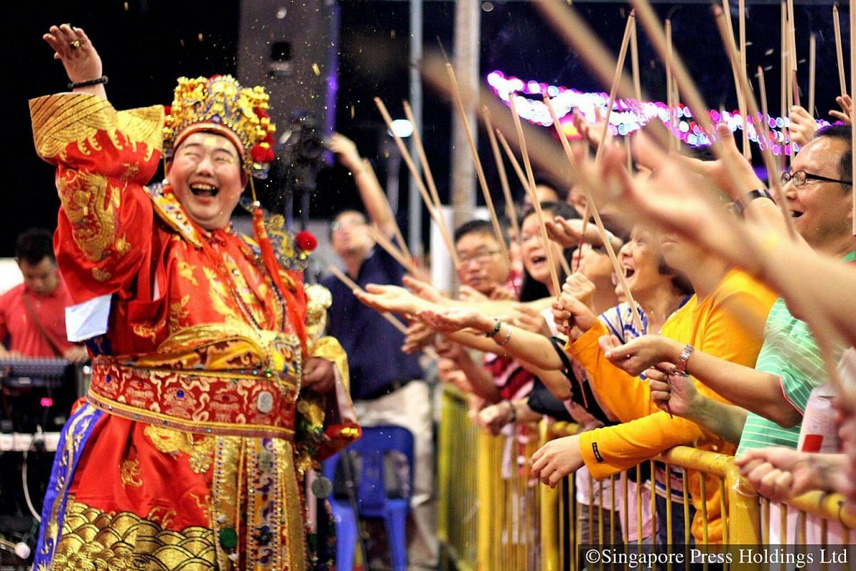 2014: This portly man decked out as the God of Fortune, showers gold flakes on devotees, symbolising the spread of prosperity, at Loyang Tua Pek Kong Temple on Chinese New Year Eve. The God of Fortune, or cai shen ye, has always been a major crowd-pu