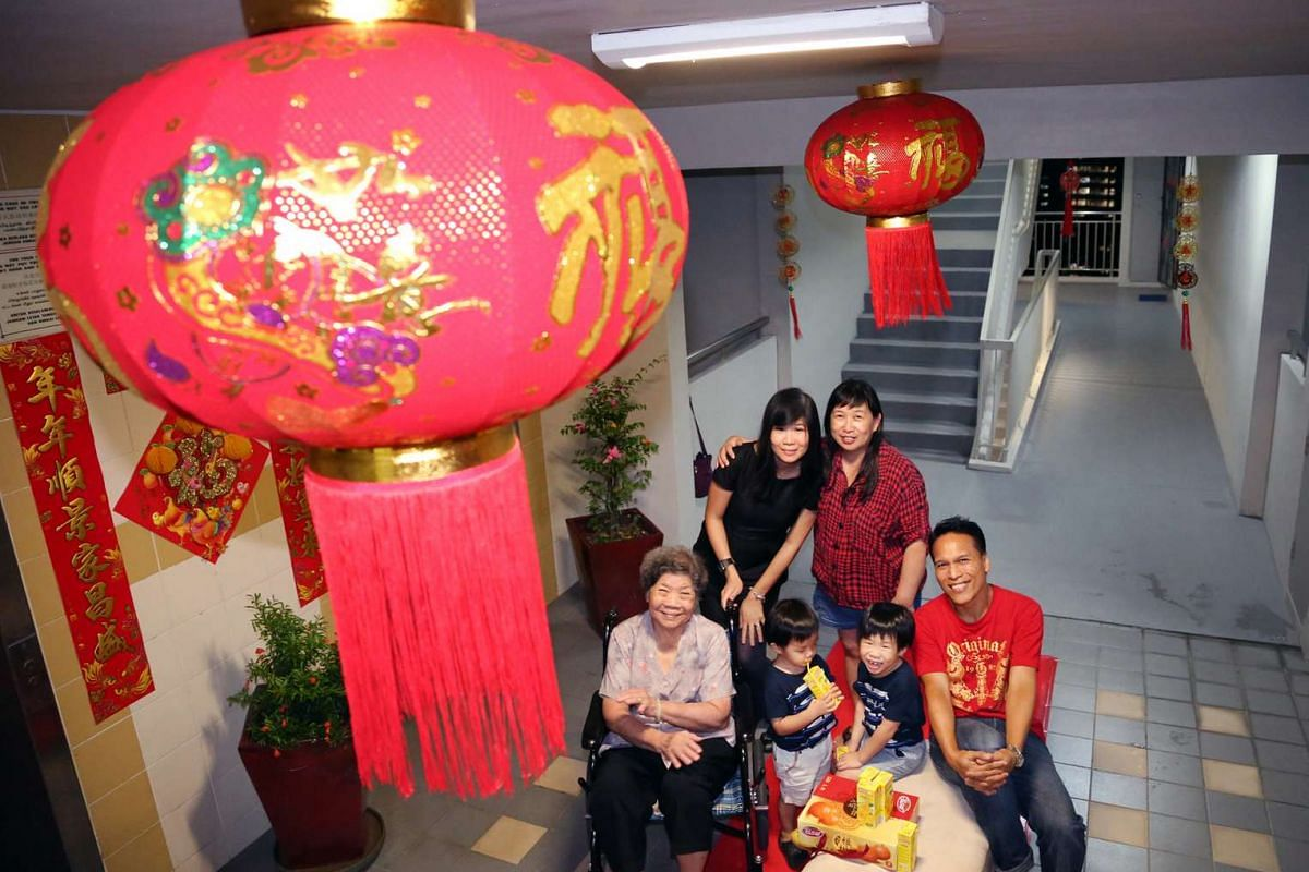 Mr Hamzah Osman, 46, with his neighbours. He placed decorations outside the lift area, putting up lanterns, lunar new year couplets, a red carpet and a small sofa, to celebrate Chinese New Year with his neighbours.