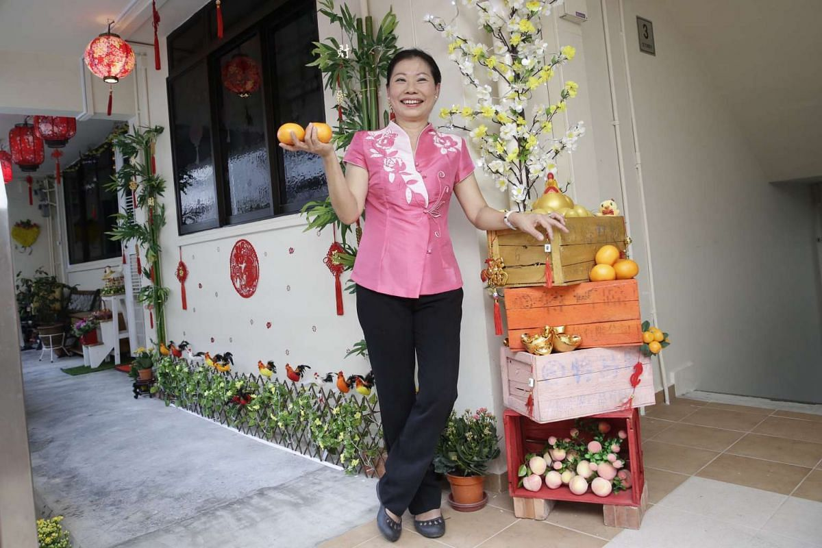 Sales promoter Linda Cheng with her Chinese New Year decorations, featuring golden eggs in the common area and other rooster-themed ornaments.