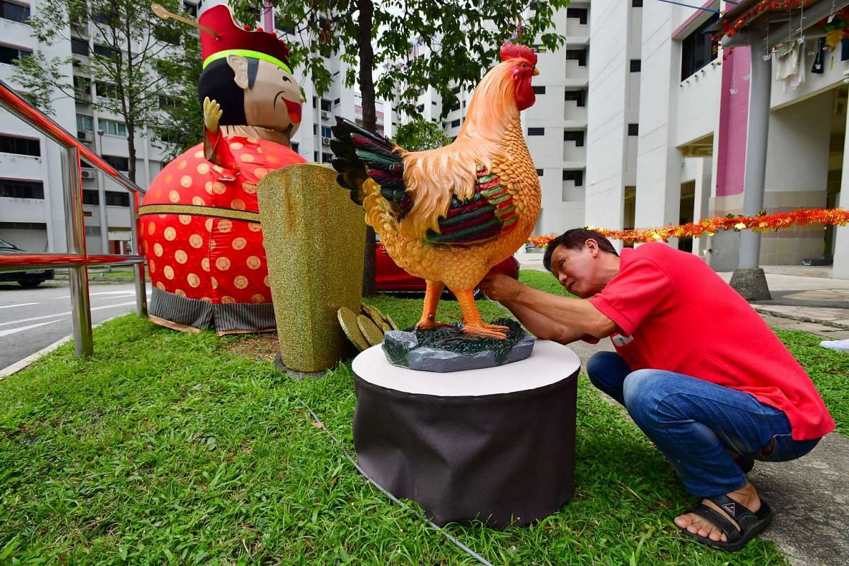 Mr Tan putting batteries into the chicken so that it can make clucking sound.