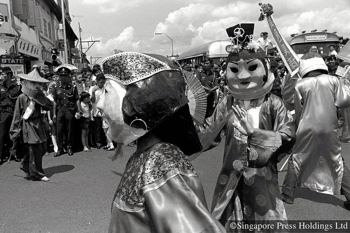"""1973: """"Bighead dolls"""" drawing laughs during the parade. Thousands of people throng the streets to watch the procession make its way from Jalan Besar to Outram Park. Some 2000 performers from different Chinese associations took part."""