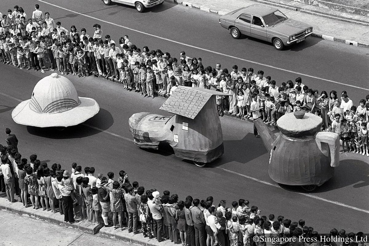 1973: Crowds lining both sides of the street as they watch a procession of floats.