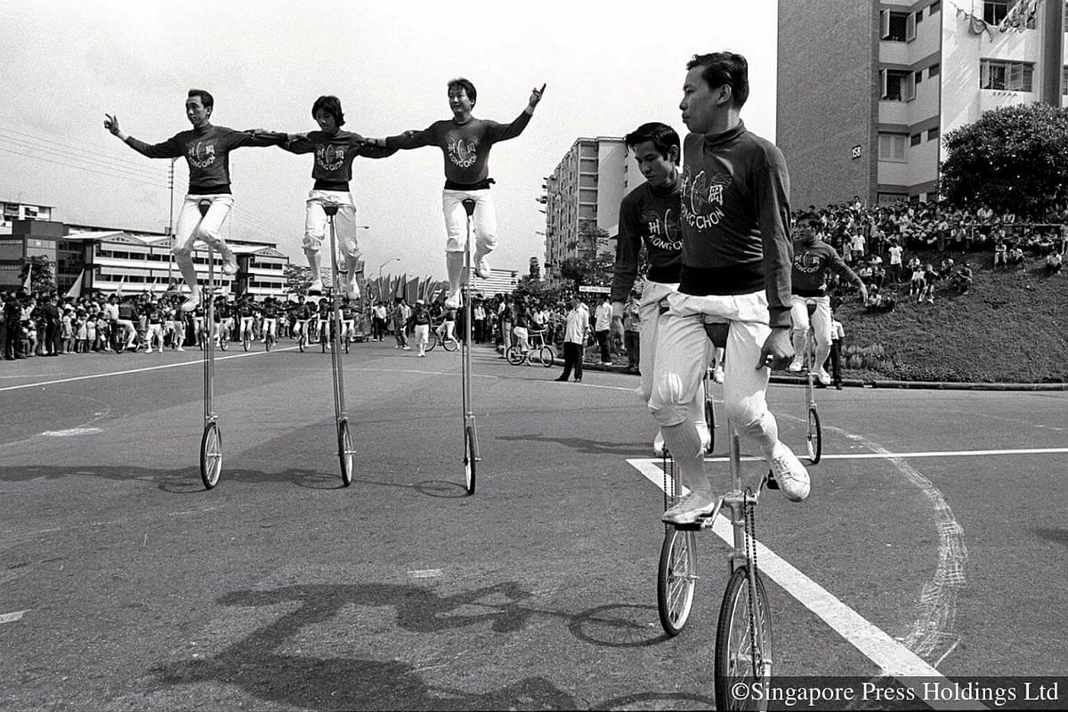 1975: Thousands of people in holiday mood lining the roads in Queenstown to watch the Chingay parade. Drawing applause from the enthusiastic crowd are the Kong Chow pugilists on wheels, performing tricks on their unicycles.