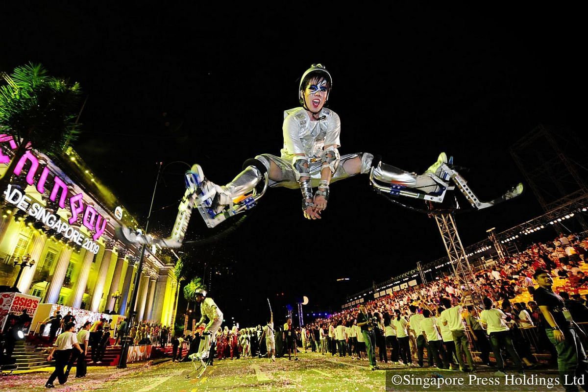 "2009: A student togged up in ""sky-running"" gear taking a leap into the air at the end of the Chingay parade. An after-parade party, called City Alive!, is organised by the People's Association Youth Movement (PAYM) to give the youth an opportun"