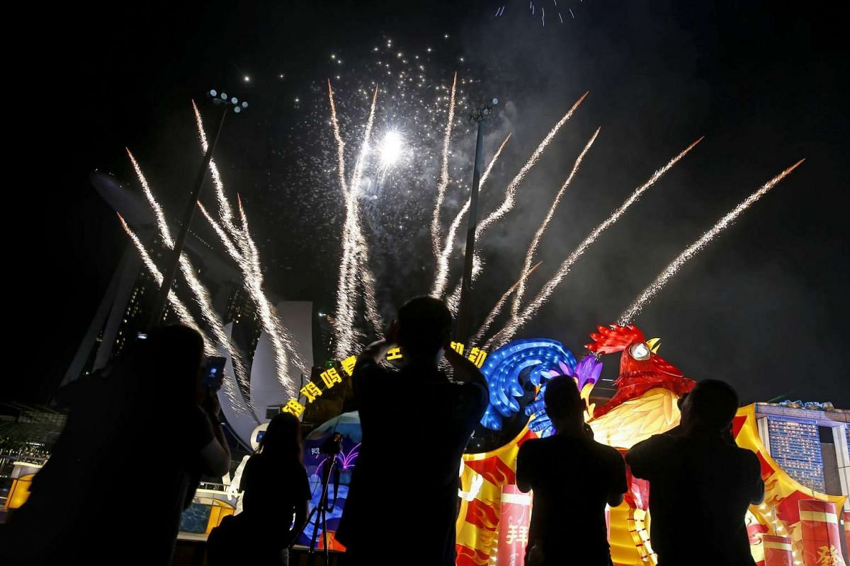 Visitors observing fireworks explode over the illuminated sculptures as part of the River Hongbao celebrations, on Jan 26, 2017.