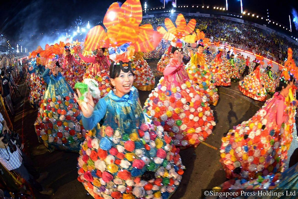 """2015: Can-can dancers from 11 community clubs and residents' committees twirling in their colourful costumes bedecked with """"We Love SG"""" plastic flowers at the opening of Chingay 2015. The flowers are made using recycled plastic bags."""