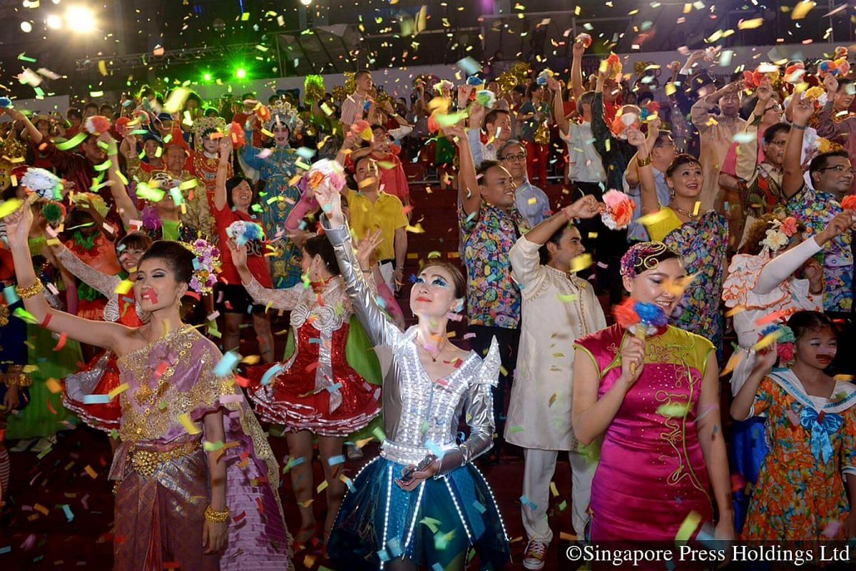 """2015: Representatives from 230 local and 17 international groups taking part in the parade, raising their """"We Love SG"""" flowers under a shower of confetti. In celebration of Singapore's 50th anniversary of independence, the Chingay parade is the big"""
