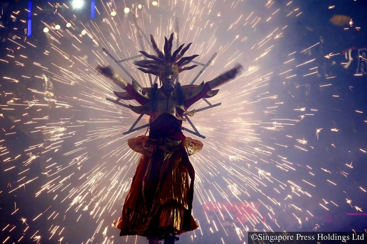2016: A stiltwalker becomes partially silhouetted as a quick pyrotechnic display emanating from the back of his body dazzles the crowd during the opening night of the Chingay parade.