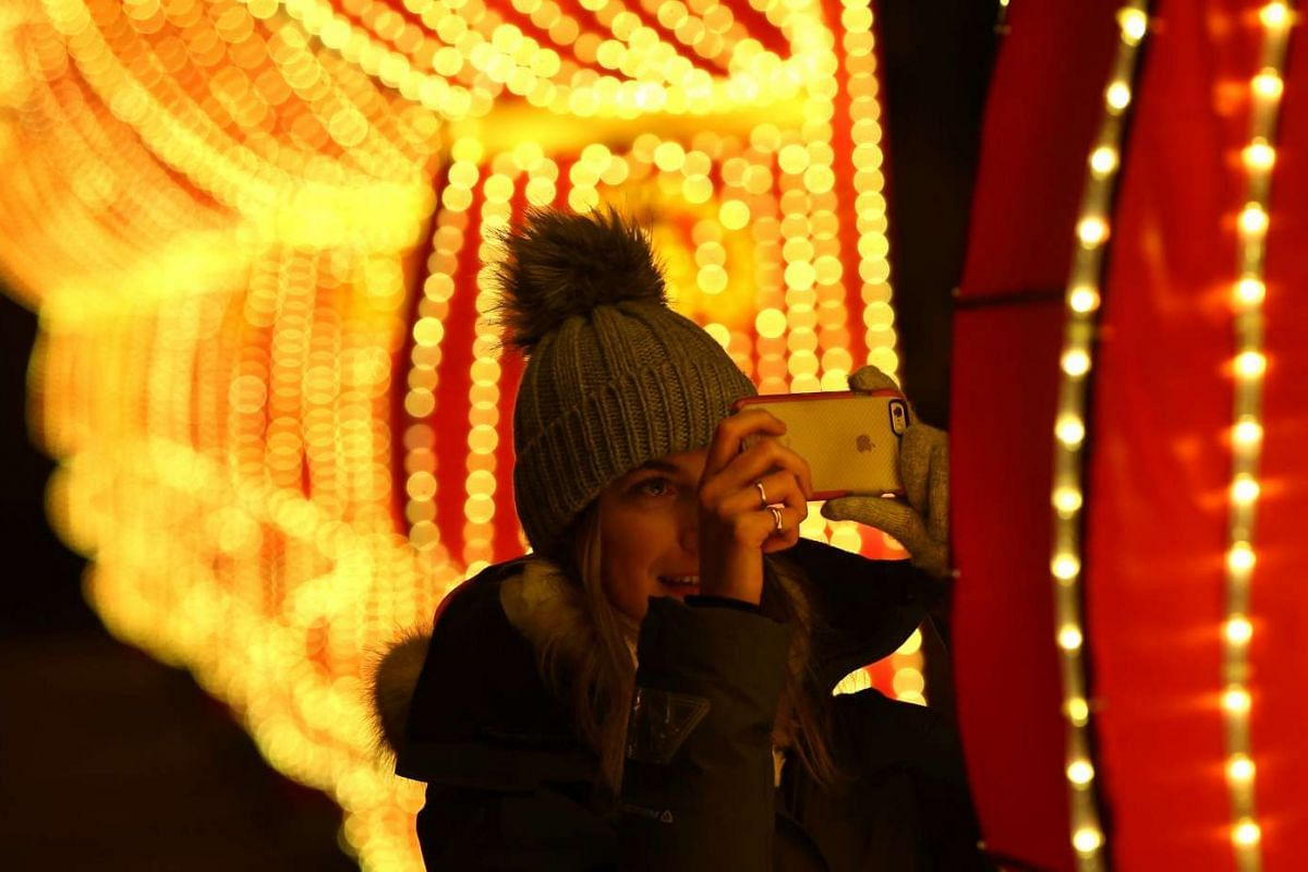 A woman photographs a light display during the The Magical Lantern Festival marking Chinese New Year at Chiswick House in London on Jan 18.