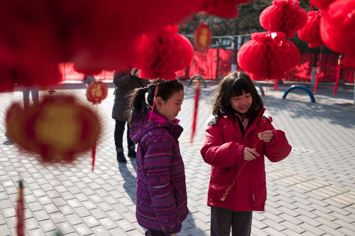 Children stand near a lantern tree display ahead of Chinese New Year in Beijing on Jan 24. Chinese New Year is known locally as the Spring Festival.