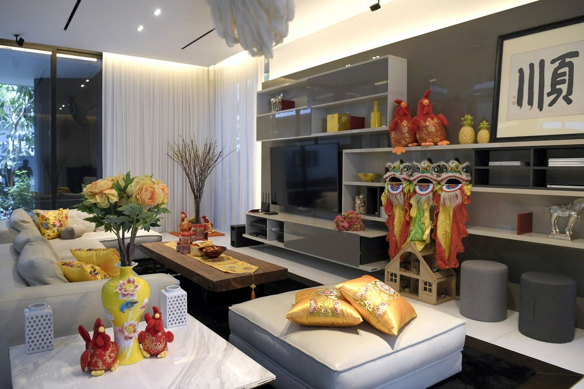 The home of Mr Zoyd Teo, his wife Clarissa, and their three children. Peppered around their living room are nine rooster soft toys and on the shelf are three lion heads.