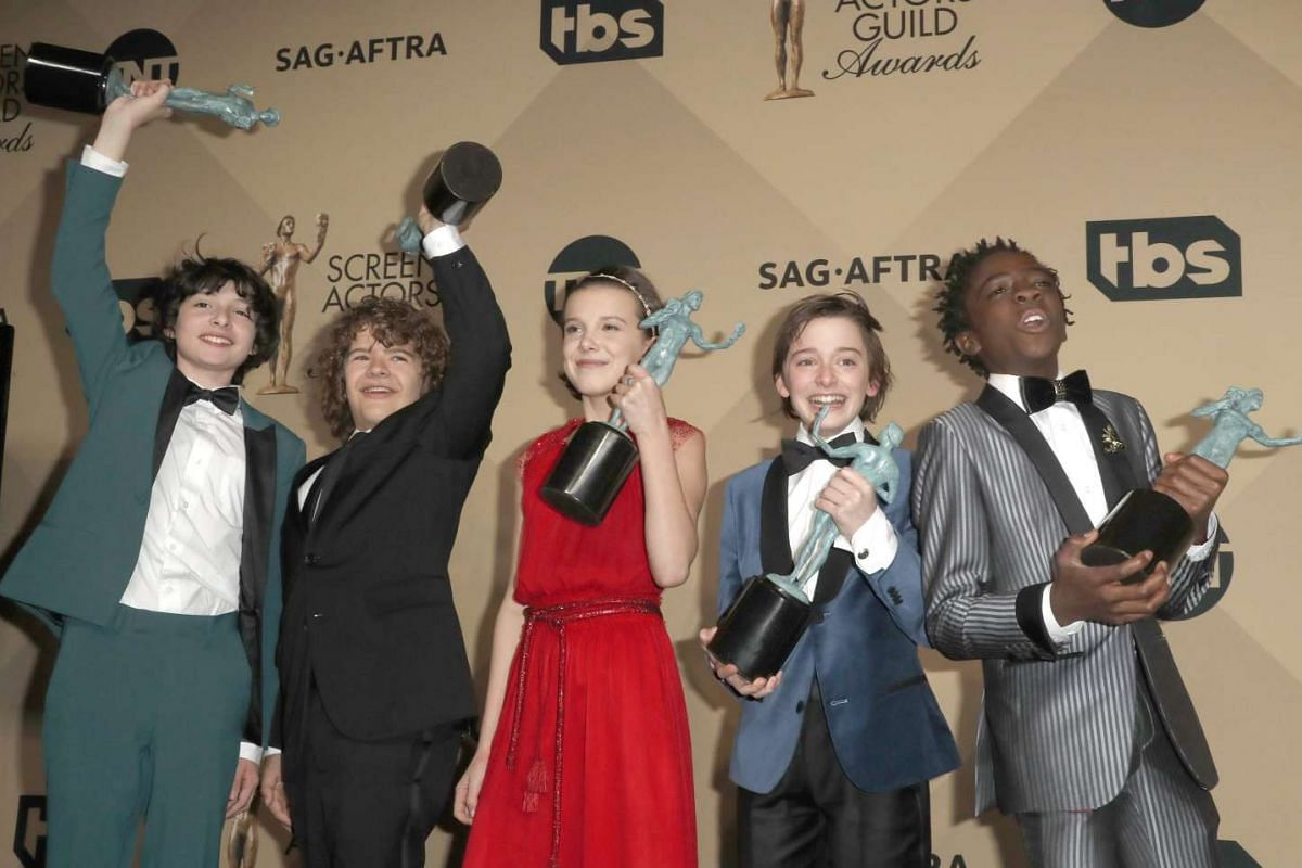 (From left) Finn Wolfard, Gaten Matarazzo, Millie Bobby Brown, Noah Schapp and Caleb McLaughlin, cast members of Stranger Things, pose with the SAG Award for Outstanding Performance by an Ensemble in a Drama Series at the Shrine in Los Angeles, Calif