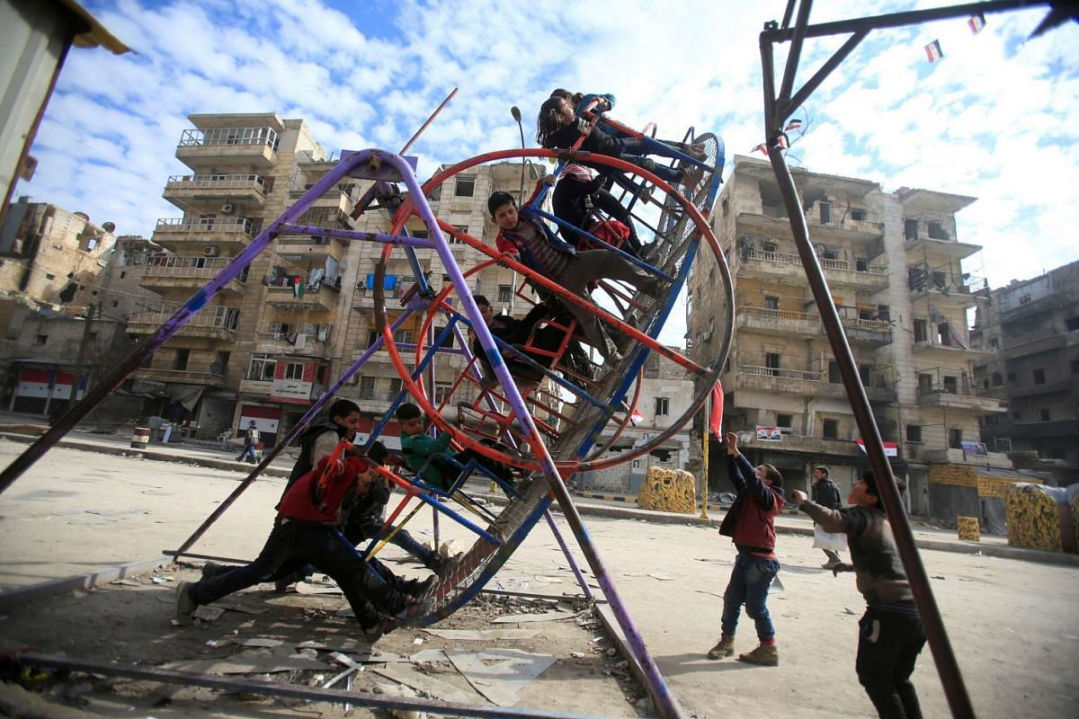 Children play on a swing in a damaged neighbourhood in Aleppo, Syria on Jan 30, 2017.