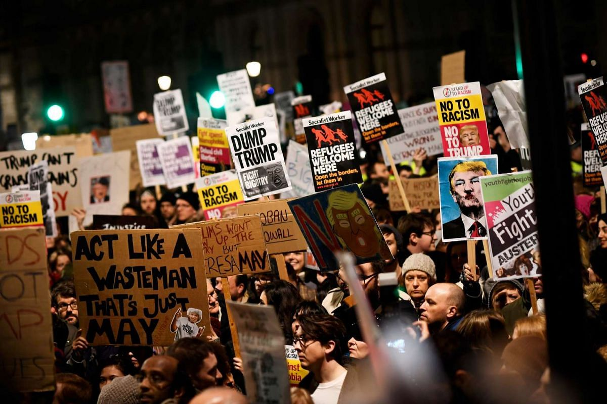 Demonstrators hold placards during a protest against US President Donald Trump's executive order travel ban in London, Britain on Jan 30, 2017.