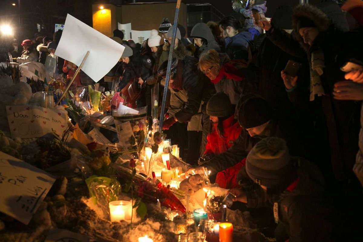 People leave candles and flowers across from the Quebec Islamic Cultural Centre, at a memorial made in honour of the victims of a shooting at the mosque in Quebec City, Quebec on Jan 30, 2017.