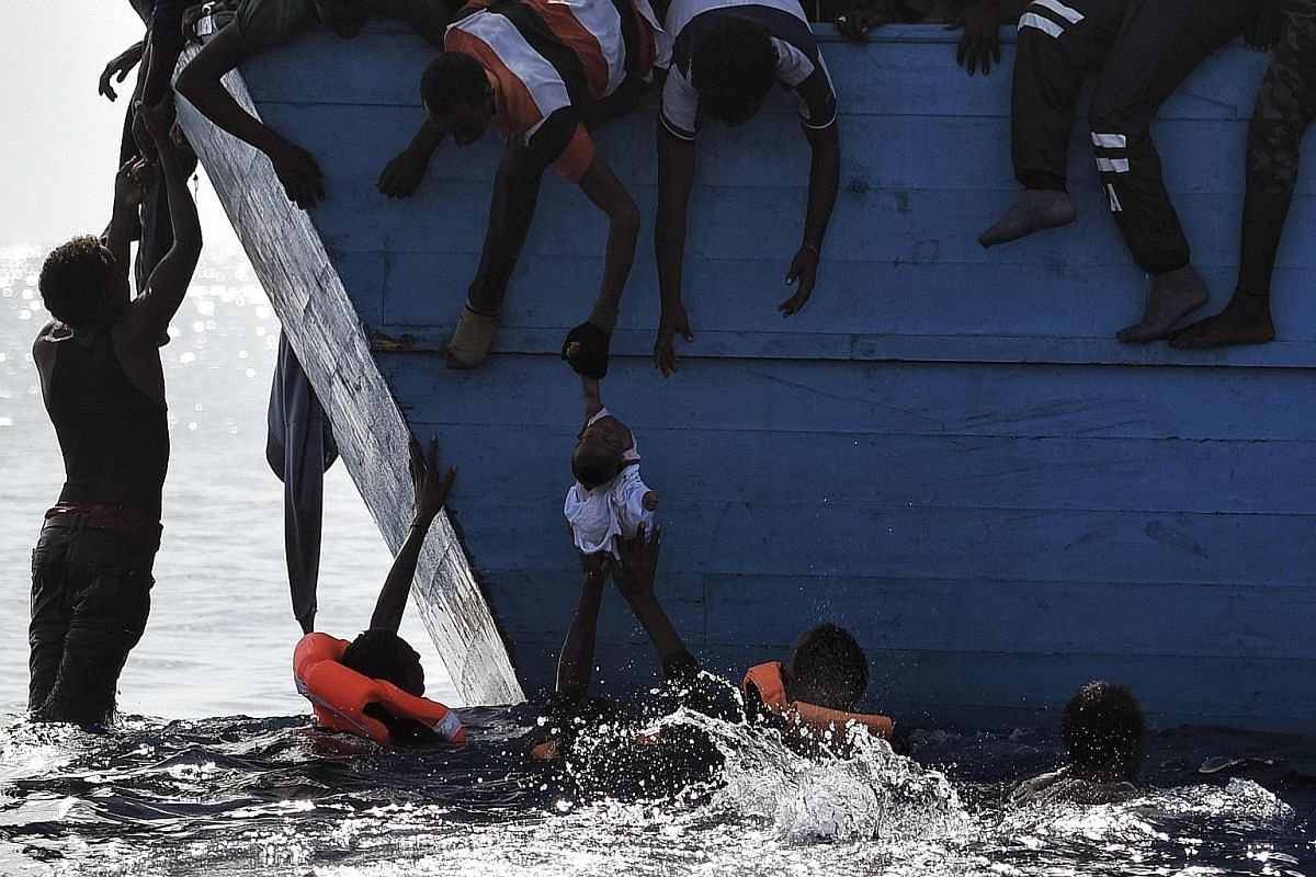 Migrants rescuing a child as they themselves wait to be rescued by members of Proactiva Open Arms non-governmental organisation in the Mediterranean Sea, some 12 nautical miles north of Libya, on Oct 4 last year. For migrant children, surviving is ju