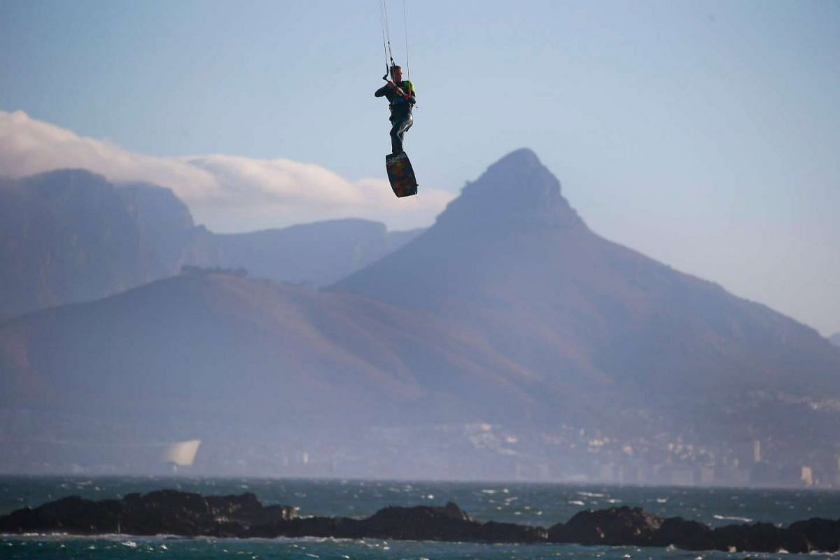A kiteboarder soars through the air while he warms up ahead of the opening rounds of the Red Bull King Of The Air competition in Big Bay, Cape Town, South Africa on Jan 31, 2017.