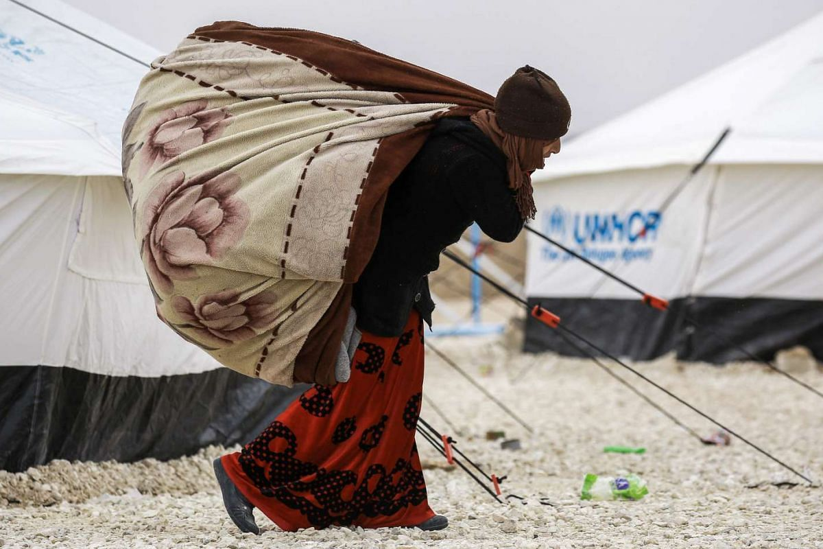 A displaced Syrian woman from Deir Ezzor carrying heavy blankets as she walks through the falling snow in a refugee camp in al-Hawl, Syria, on Feb 1, 2017.