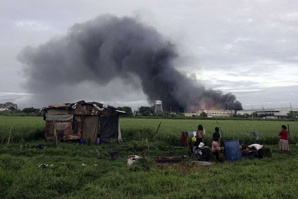 Filipino villagers looking at a burning factory in the town of General Trias, Cavite province, the Philippines, on Feb 2, 2017.