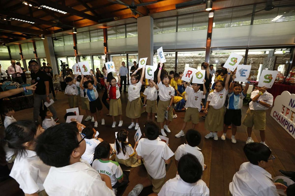 "Yu Neng Primary School pupils hold up the letters for the word ""rhinoceroses"" which clinched their win during the game of ""human Scrabble"" at the launch of the fifth RHB-The Straits Times National Spelling Championship (The Big Spell) at the"