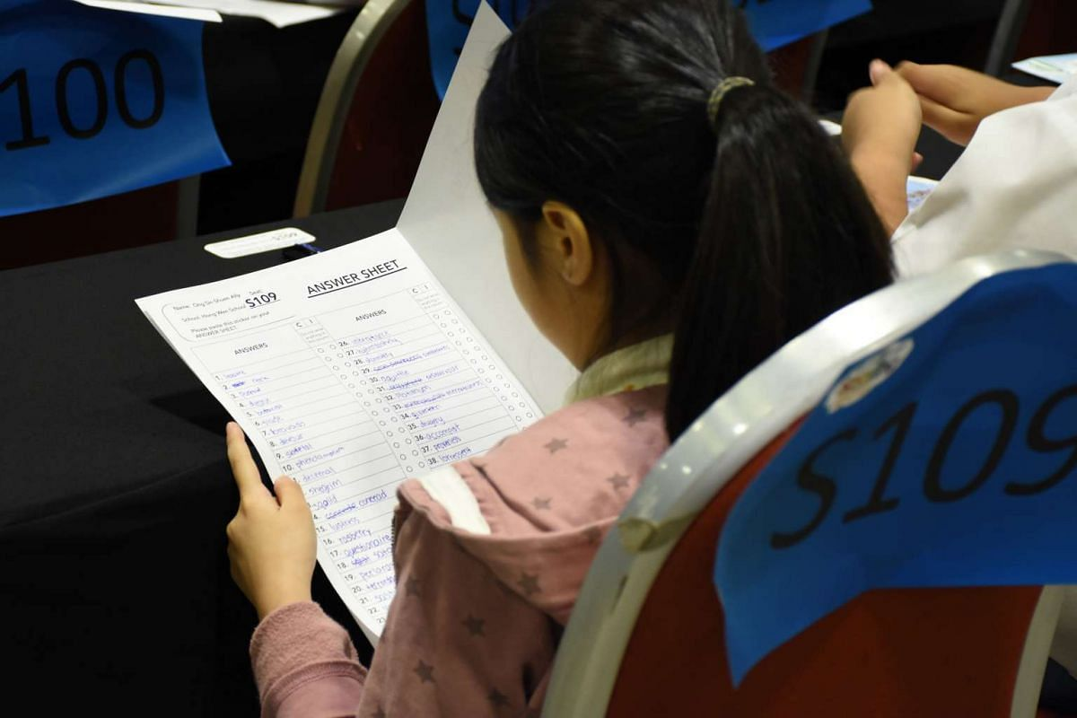 A pupil writing down her answers in the first round of RHB-ST National Spelling Championship held at the Suntec Singapore Convention & Exhibition Centre on Mar 26, 2016.