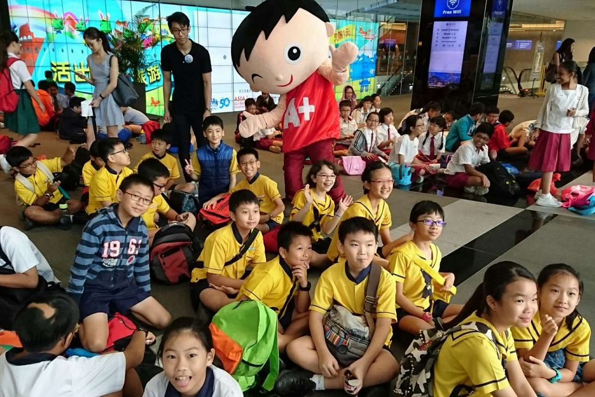 Little Red Dot's Motivated Dot mascot interacting with participants at the holding area of The Big Spell 2016 preliminary round at Suntec Singapore Convention and Exhibition Centre.