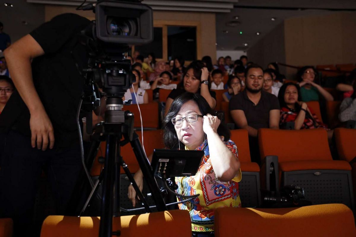 "Mrs Soo Kim Bee, a master teacher and arbitrator in the North zone, checking the video playback for the part where the contestant spelt ""dominant"", during the zonal round of the RHB-The Straits Times National Spelling Championship 2016."