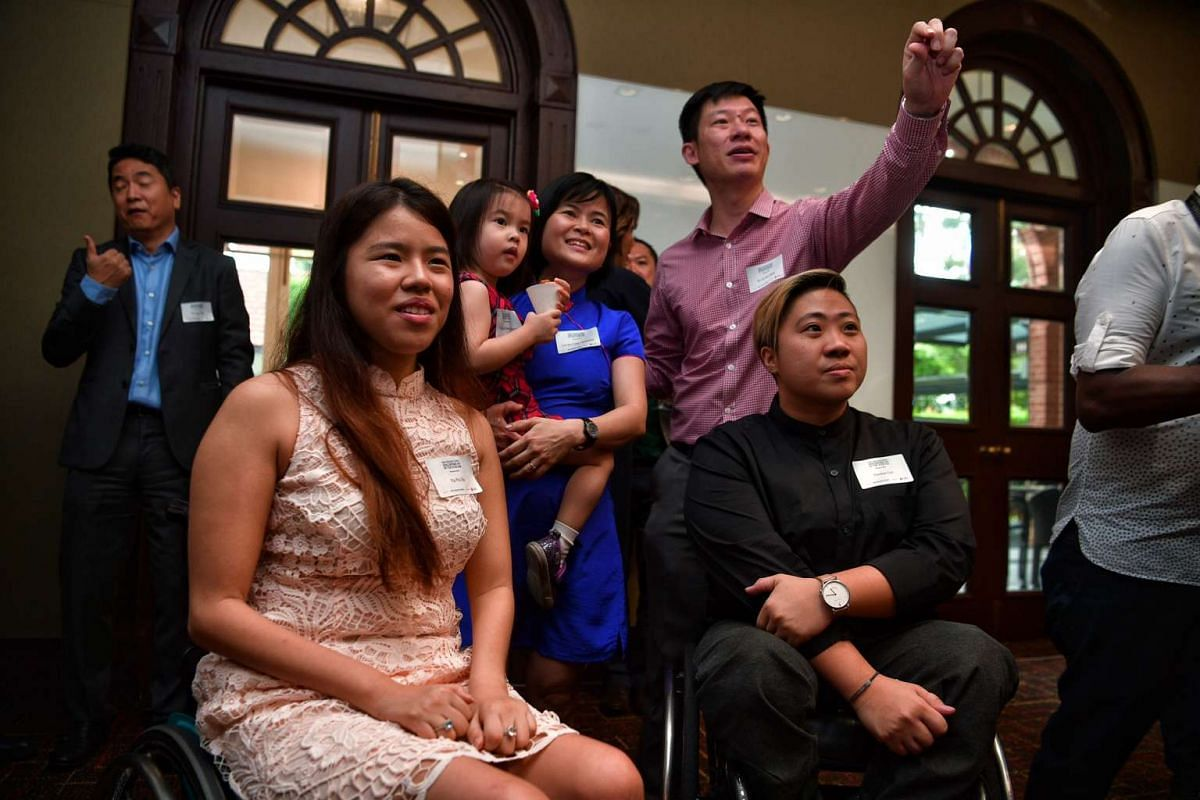 Paralympians Yip Pin Xiu and Theresa Goh take pictures with Dr Chi Wei Ming and his family.