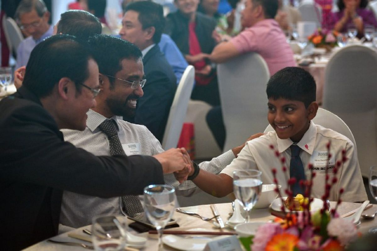 Ashvin Gunasegaran (right) beams as he is congratulated during The Straits Times Singaporean of the Year 2016 award ceremony.