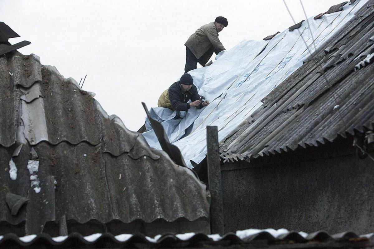 Men repairing the roof of a building damaged after shelling in Avdiivka, Donetsk area, Ukraine, on Feb 5, 2017.