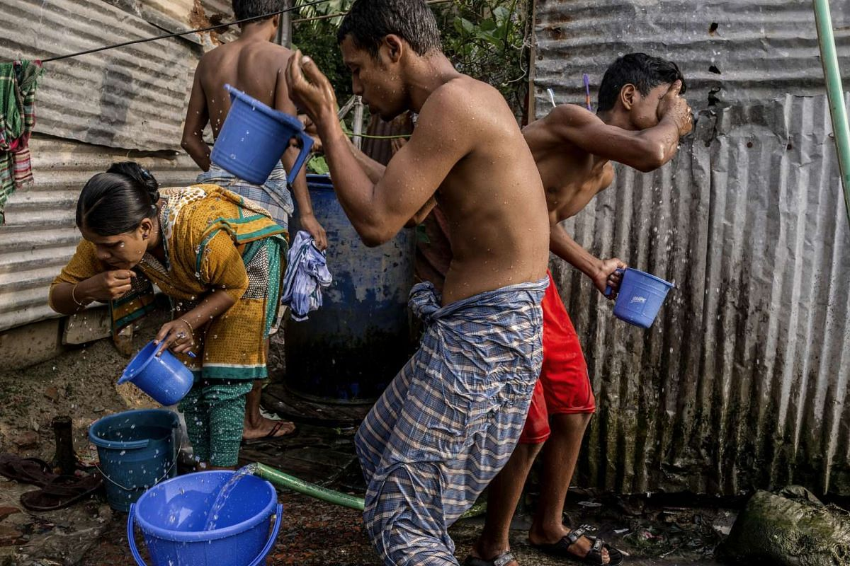 People collecting water from various pipes for use in cooking, drinking and bathing, in the Korail slum in Dhaka, Bangladesh, on Aug 19, 2016.