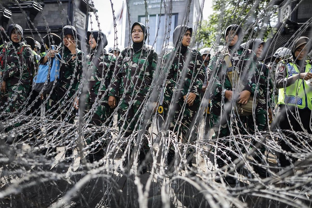 Military personnel (far left) on guard outside the Jakarta police HQ last month as cleric Rizieq Shibab (left) arrived for questioning over allegations of defamation. Jakarta Governor Basuki Tjahaja Purnama at a concert last week ahead of this month'