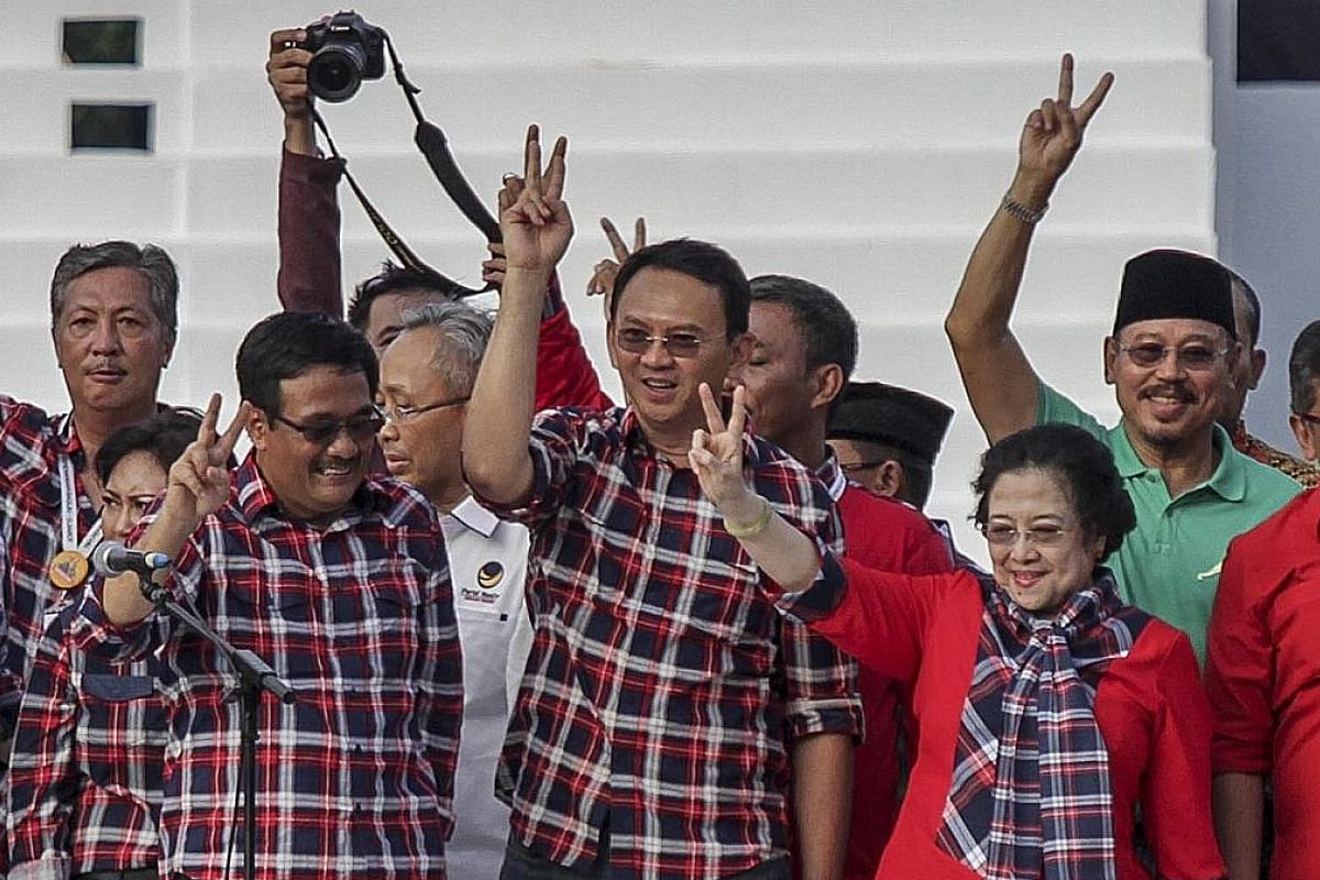 (Front row, from left) Running mates Djarot and Basuki with former Indonesian president Megawati at a campaign concert on Saturday. The pair are backed by Ms Megawati's PDI-P. The most recent polling released by Charta Politika last week shows them i