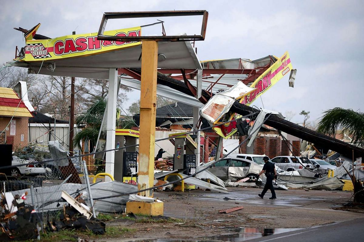 A police officer walks through a damaged gas station along Chef Menture Ave after a tornado in New Orleans, Louisiana, on Feb 7, 2017.