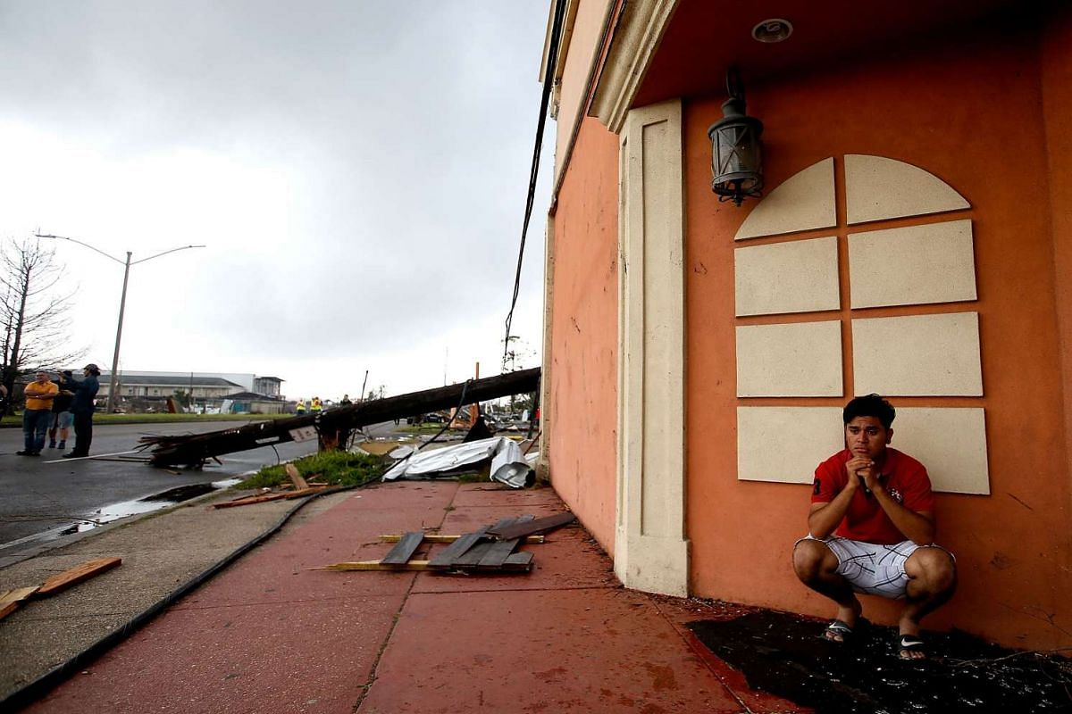 A man sits next to the side of a building after a tornado in New Orleans, Louisiana, on Feb 7, 2016.