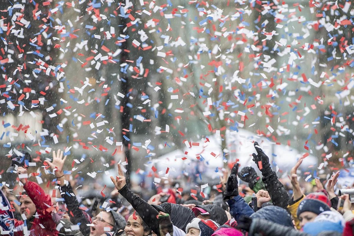 Fans cheer with confetti in the air as they watch the New England Patriots Super Bowl victory parade on Feb 7, 2017, in Boston, Massachusetts.