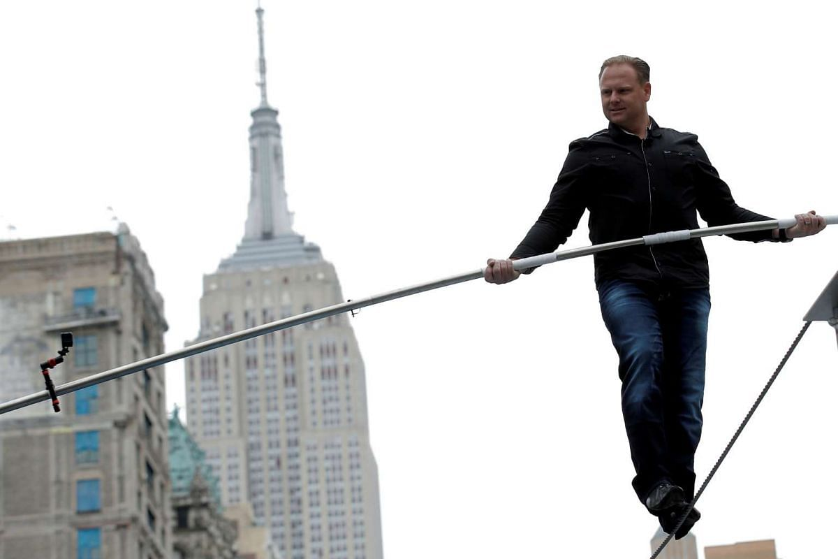 Aerialist Nik Wallenda walks a tightrope during a promotional event in midtown Manhattan, with the Empire State Building behind him, in New York City on May 17, 2016.