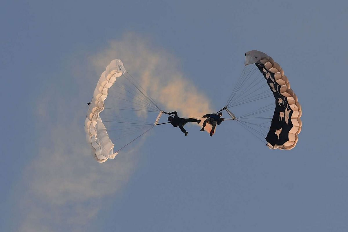 Members of a local parachute group perform stunts during the annual International Hot Air Balloon Festival at the former Clark US Air Force base in Pampanga province, north of Manila on Feb 9, 2017.