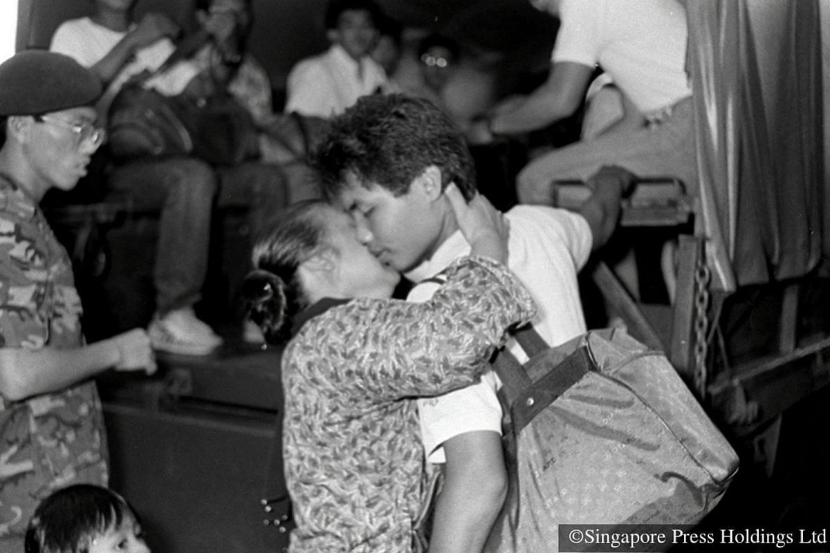 1987: A mother bids teary farewell to her son, kissing him before he boards the three-tonner on enlistment day.