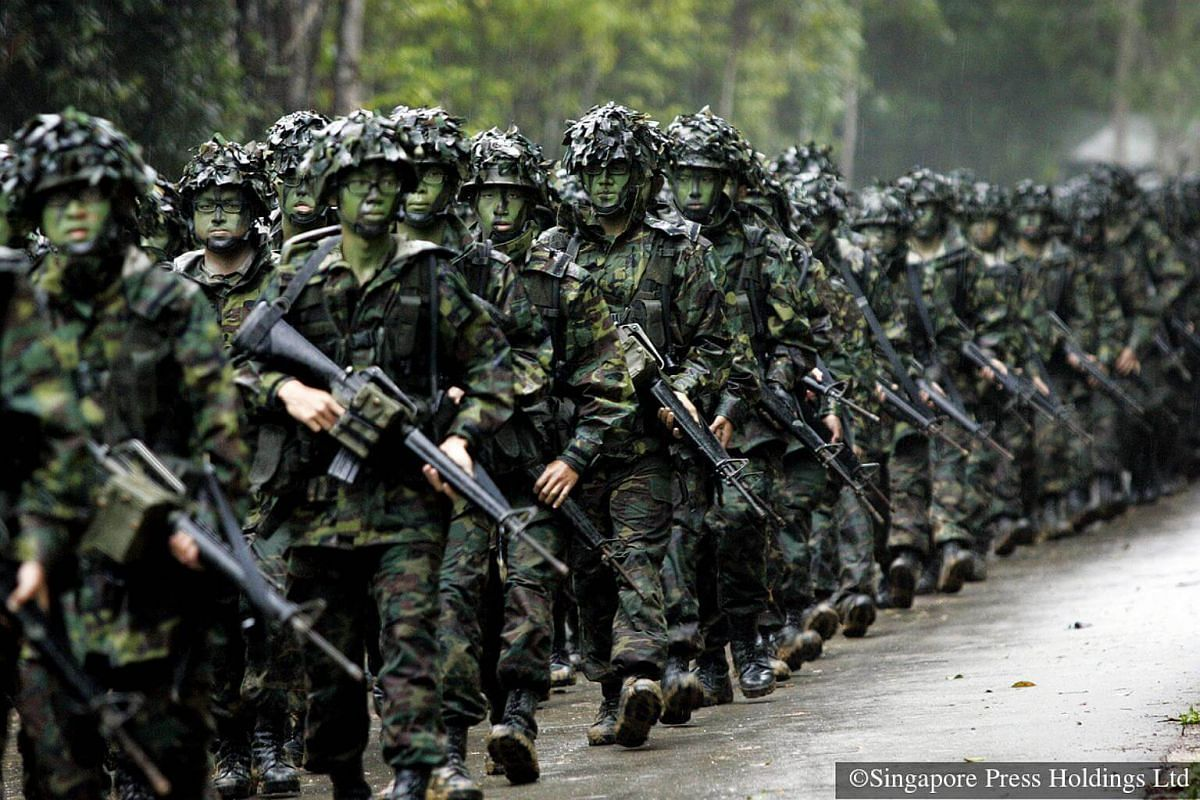 2007: At the end of a six-day field camp in Pulau Tekong, recruits march briskly to a new location complete with field packs, Load Bearing Vests and M16 rifles.