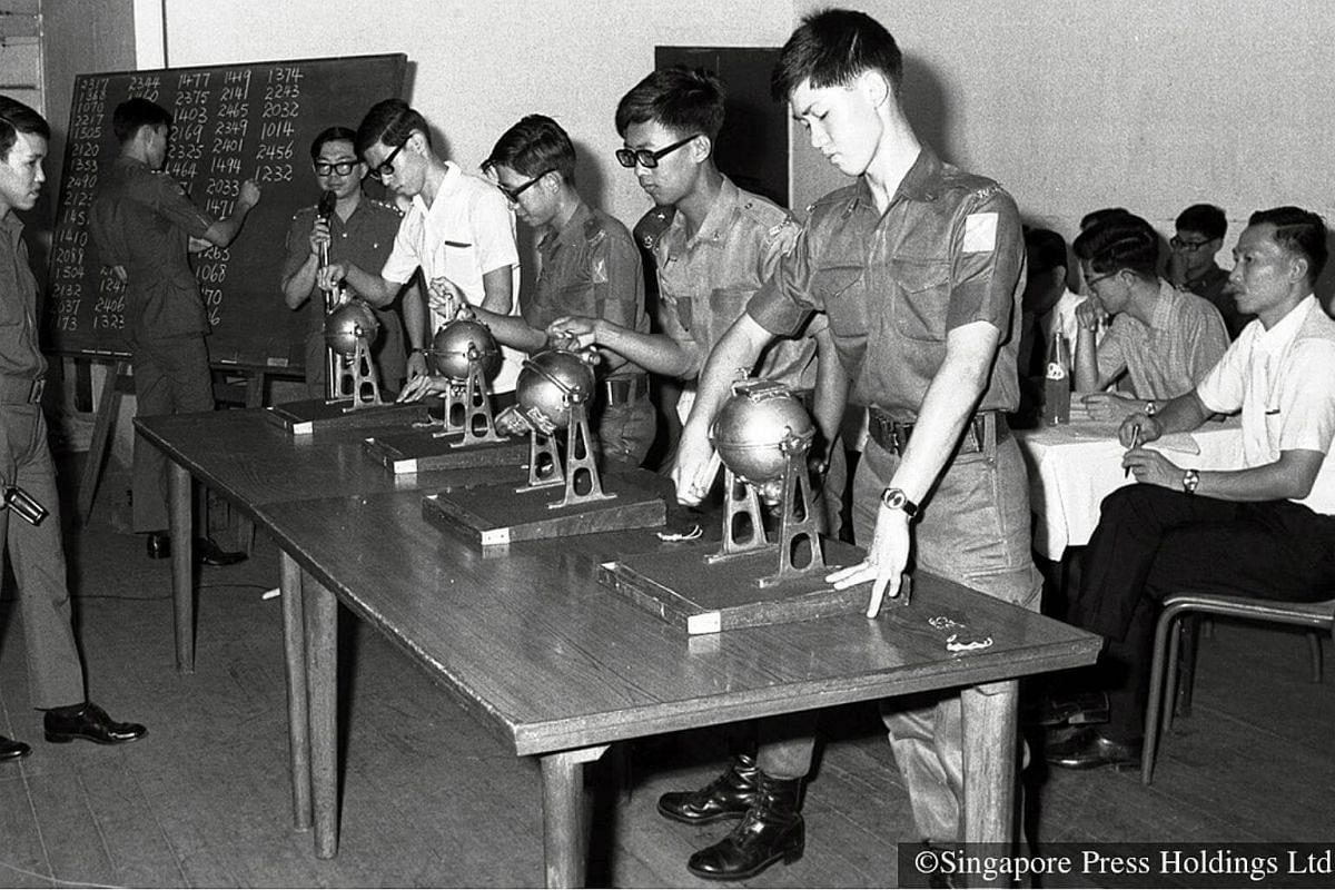 1971: The first ballot at the Beach Road camp to defer NS call-up for tertiary education. SAF personnel operating the four balloting drums while other officers write the numbers of SAF recruits on the board during the draw.
