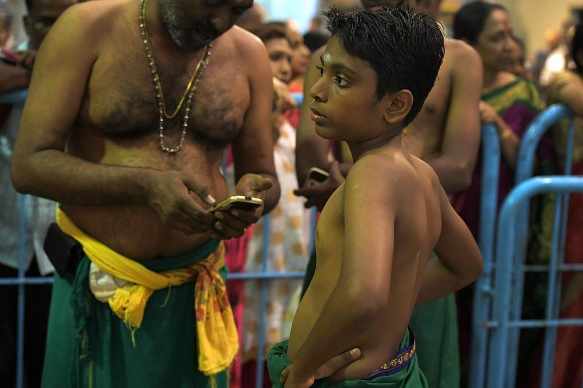 Devotees waiting for the installation of Sri Murugan in the temple as the chariot carrying Sri Murugan arrives at the Sri Thendayuthapani Temple on the evening of Feb 8, 2017.  Anyone below 16 years old is allowed only to carry a Paal Kudam - a pot o