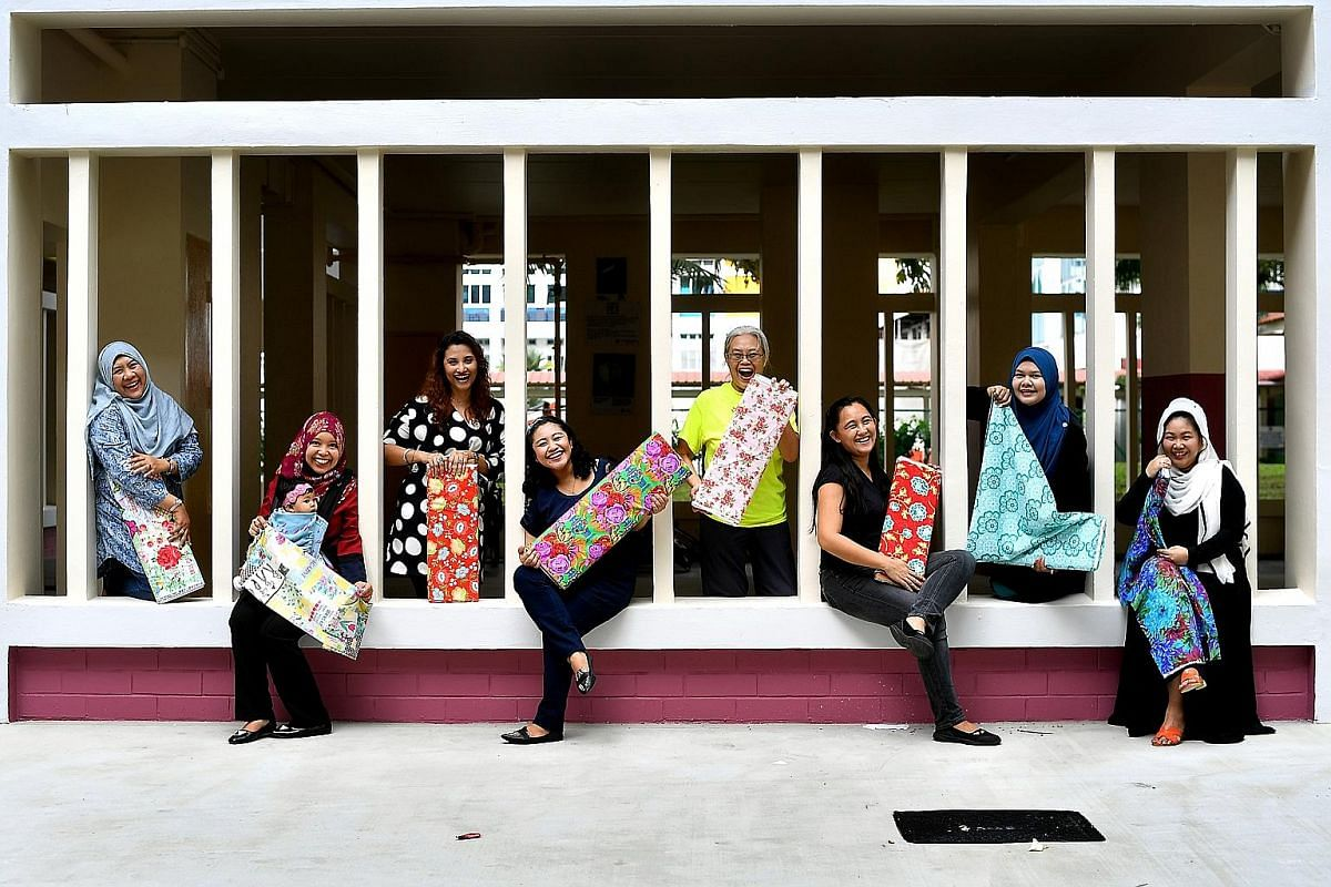 Co-founder of Sew Into It Amy Toh (standing) with her students Ng Hui Ling (sitting) and Ms Ng's daughter, Janelle, who learnt to make messenger bags. Members of Pasir Ris Sewing Ladies (from far left) Ms Romnah Omar, Ms Suhaila Jamat, Ms Hamidah Mik