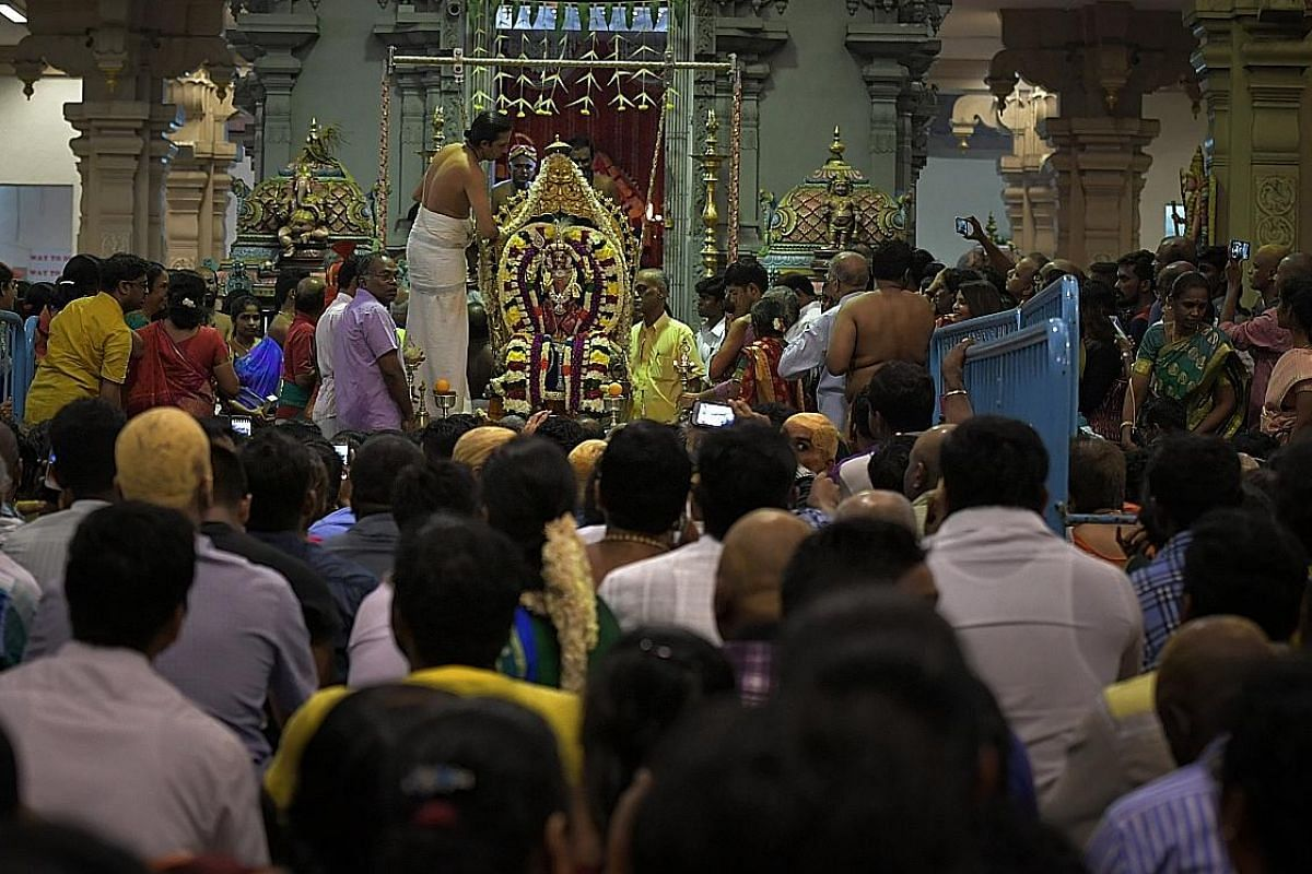 A devotee, with her tongue pierced as a form of sacrifice, carrying a pot of milk during the procession which began at Sri Srinivasa Perumal Temple in Serangoon Road yesterday. Devotees carrying kavadis - some with steel rods that pierce their skin (